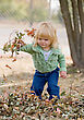 Little Girl Playing in the Leaves - stock photo