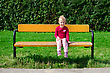 Stock Photo : Smiling Stock Photo: Little Girl Sitting On The Bench In The Park
