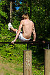 Man Pull-ups On A Bar In A Forest. From The Back. - stock photo