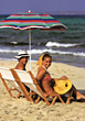 Man and woman sitting in beach chairs smiling