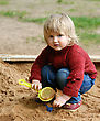 Playful Stock Photography: Portrait Of A Child - A Little Girl Playing With Sand