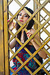 Pretty Young Brunette Behind A Wooden Lattice