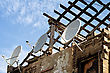 Ruined Building With Stripped Roof Exposing The Roofing Timbers To The Sky And A Row Of Three Satellite Dishes On The Exterior Grungy Wall stock image