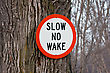 Stock Photo : Navigation Stock Image: Slow No Wake Sign Nailed To A Tree
