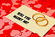 Stock Photo : Celebrate Stock Photo: Two Rings And A Card With Marriage Proposal On The Red Background