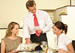 People Eating  Waiter Serving Female Friends Dining at Restaurant stock photography
