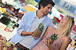Young Couple Holding Pineapples At A Market Stall
